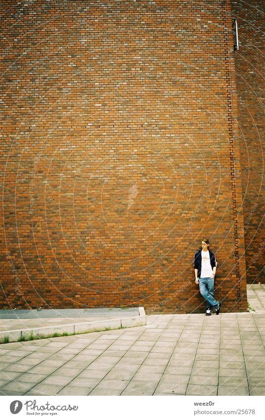wenigkeit Mensch Jugendliche Einsamkeit rot ruhig Haus Junger Mann kalt gelb Wand Architektur Mauer grau Stein groß warten