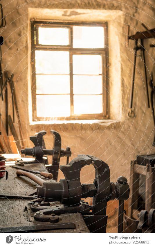 Schmiedearbeitsplatz mit Schraubstockgriff Beruf Mauer Wand Fenster alt leuchten retro Stimmung Optimismus Tradition antik Antiquität Hufschmied staubig
