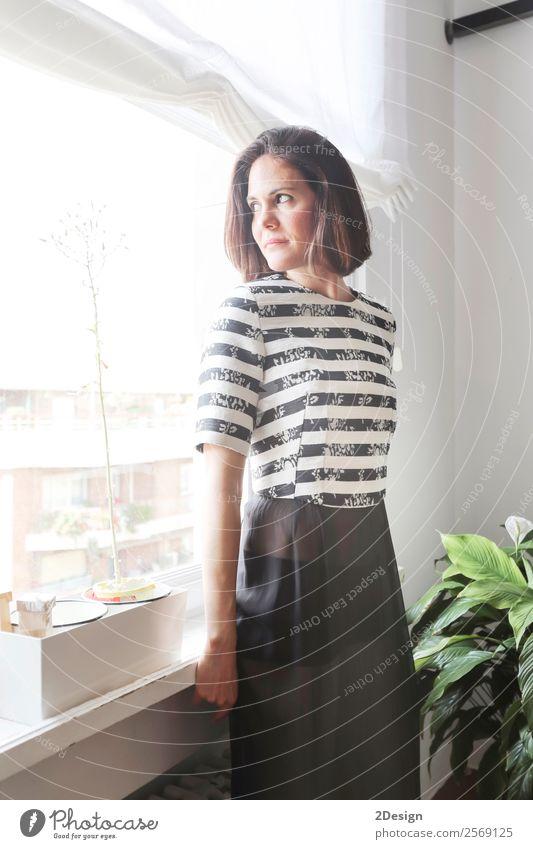 Dame, die im Wohnzimmer neben einem Fenster posiert. Reichtum elegant Stil Glück schön Körper Erholung Möbel Mensch feminin Junge Frau Jugendliche Erwachsene