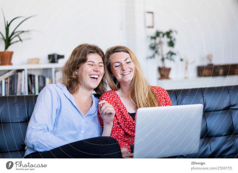 Zwei junge Frauen benutzen den Computer, während sie auf der Couch sitzen Lifestyle kaufen Glück Geld schön Leben Erholung Haus Sofa Geldinstitut Telefon PDA