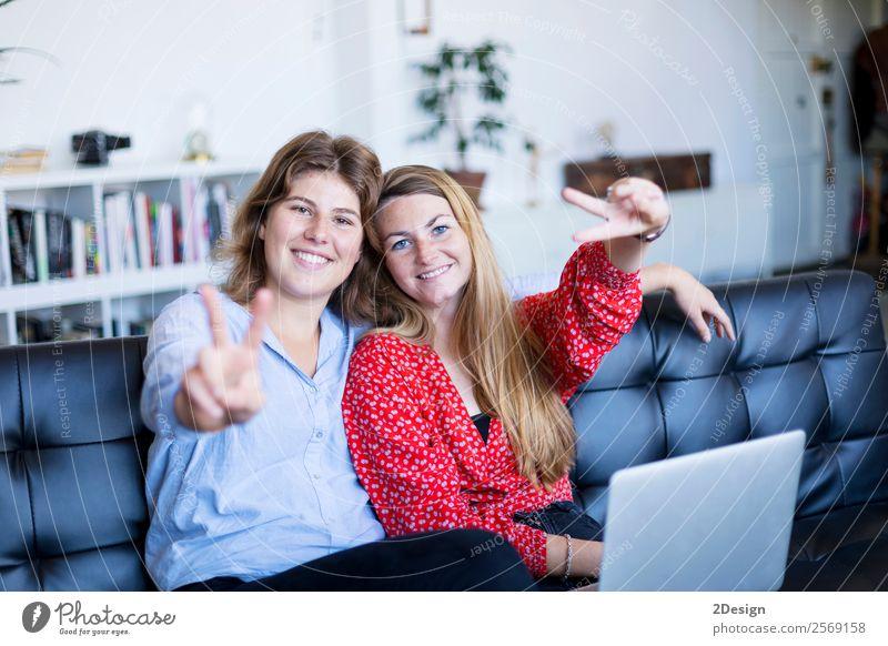 fröhliche Teenagermädchen auf einem Sofa sitzend Lifestyle kaufen Freude Glück schön Zufriedenheit Freizeit & Hobby Erfolg sprechen Computer Notebook