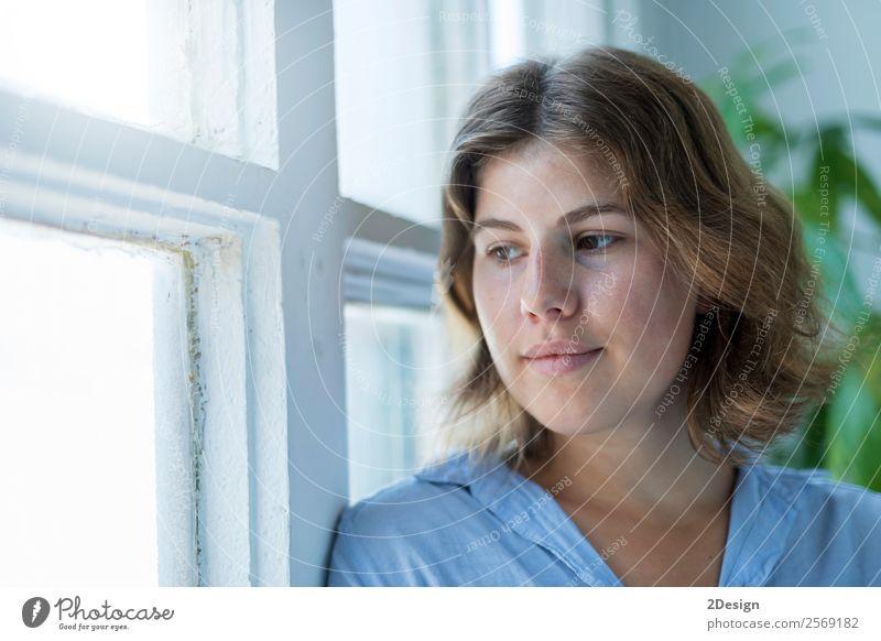 Frau, die sich an ein Fenster lehnt und aus dem Fenster schaut. Lifestyle Reichtum elegant Glück schön Gesicht Erholung Freizeit & Hobby Mensch feminin