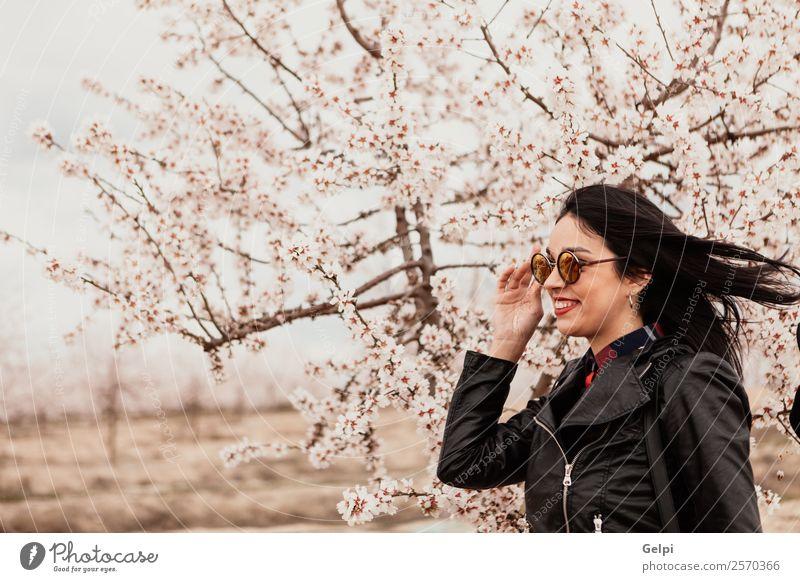 Mädchen Stil Glück schön Gesicht Garten Mensch Frau Erwachsene Natur Baum Blume Blüte Park Mode Jacke Leder Sonnenbrille brünett Lächeln Fröhlichkeit frisch