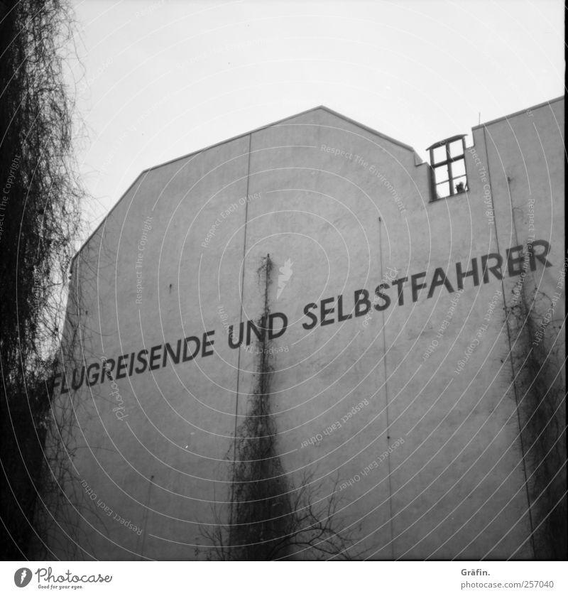 Flugreisende und Selbstfahrer Haus Gebäude Mauer Wand Stein Beton Schriftzeichen Graffiti authentisch Stadt grau schwarz weiß entdecken Surrealismus Buchstaben
