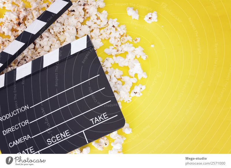 Popcorn und Klappe auf gelbem Hintergrund. Kinokonzept Fastfood Schalen & Schüsseln Freude Freizeit & Hobby Entertainment Industrie Theater Medien Fernsehen