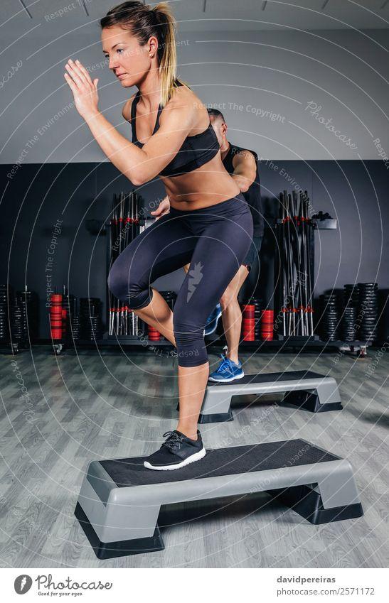 Paar, das Übungen über Schritte im Fitnessstudio macht. Lifestyle schön Körper Sport Mensch Frau Erwachsene Mann Freundschaft Liebe springen authentisch Erotik