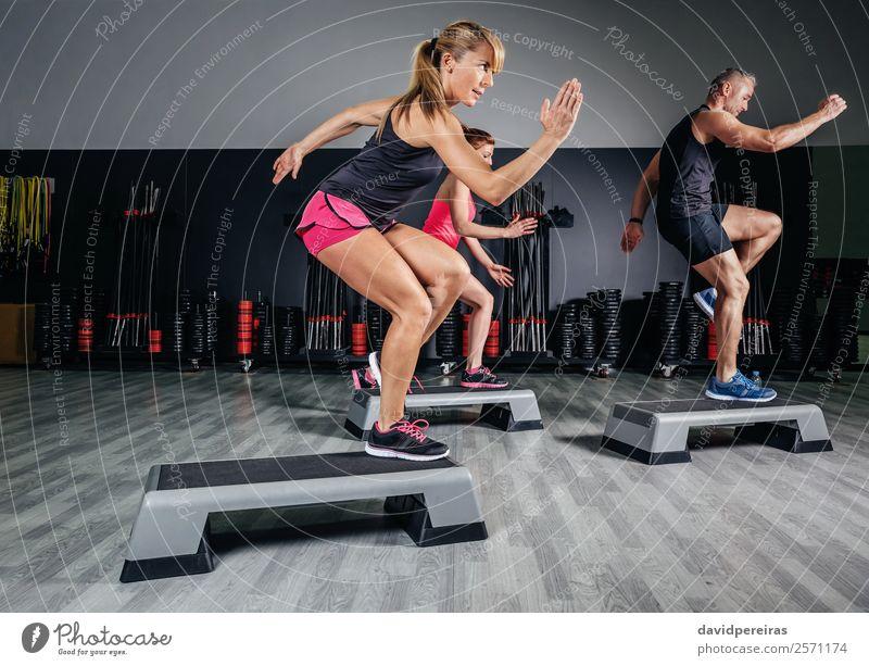 Frauentrainerin beim Aerobicunterricht mit Steppern im Fitnessstudio Lifestyle Glück schön Sport Mensch Erwachsene Mann Freundschaft Menschengruppe springen