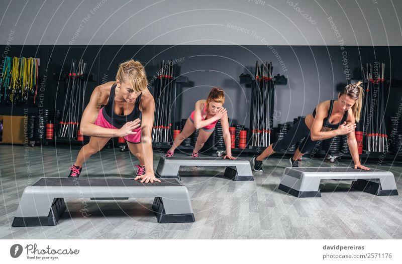Gruppentraining für Frauen über Stepper in der Aerobic-Klasse Lifestyle Glück schön Körper Sport Mensch Erwachsene Freundschaft Menschengruppe Fitness