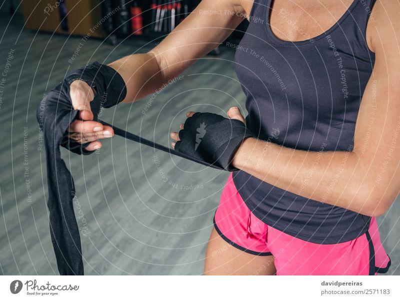 Frau wickelt die Hände mit Verbänden ein, bevor sie das Boxtraining beginnt. schön Körper Sport Mensch Erwachsene Hand Handschuhe Fitness authentisch Erotik
