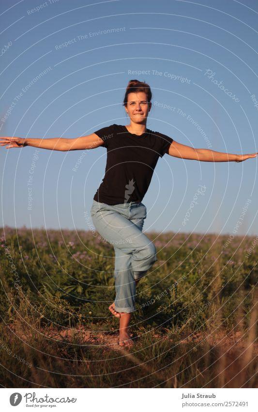 Hübsche Frau macht Yoga Übung auf einem Feld feminin Erwachsene 1 Mensch 30-45 Jahre Sonnenlicht Sommer Schönes Wetter Blume Gras Wiese T-Shirt Jeanshose