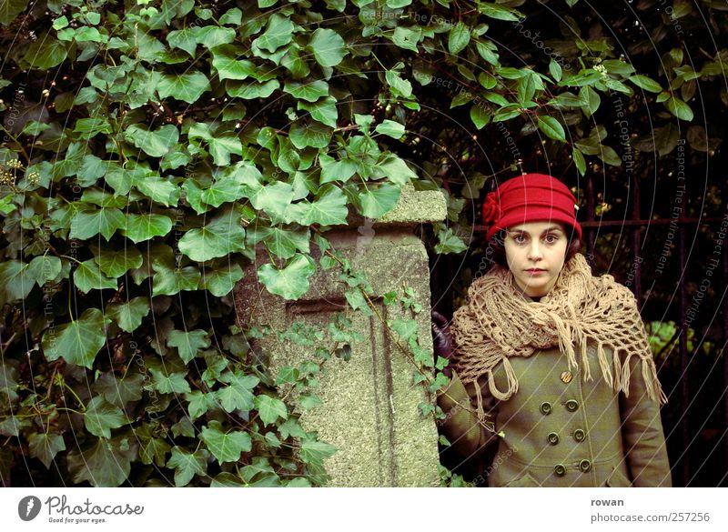 ernst Mensch feminin Junge Frau Jugendliche 1 Sträucher Blatt Mauer Wand Hut rot grün Efeu bewachsen Tor Garten Gartentor alt retro Mantel Blick Handschuhe