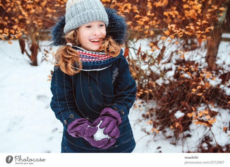 Winterportrait eines glücklichen Kindes Mädchens beim Schneeballspielen Lifestyle Freude Spielen Ferien & Urlaub & Reisen Garten Natur Wetter Wärme Park