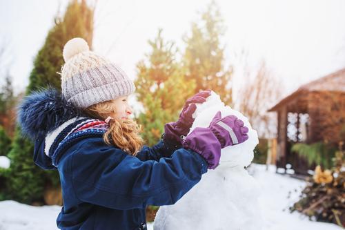 glückliches Kind Mädchen macht Schneemann in den Weihnachtsferien Freude Freizeit & Hobby Spielen Ferien & Urlaub & Reisen Winter Garten Natur Wetter Park