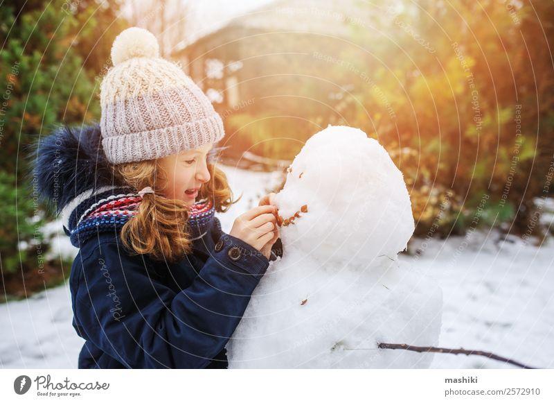 glückliches Kind Mädchen macht Schneemann in den Weihnachtsferien Freude Freizeit & Hobby Spielen Ferien & Urlaub & Reisen Winter Winterurlaub Garten Natur