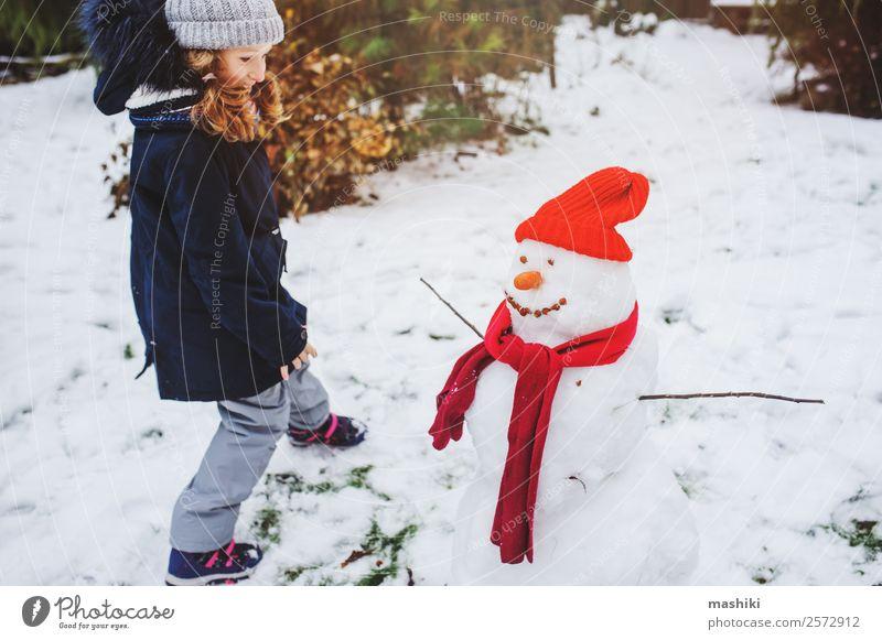 glückliches Kind Mädchen macht Schnee Mann Freude Freizeit & Hobby Spielen Ferien & Urlaub & Reisen Winter Garten Natur Wetter Park Bekleidung machen Schneemann