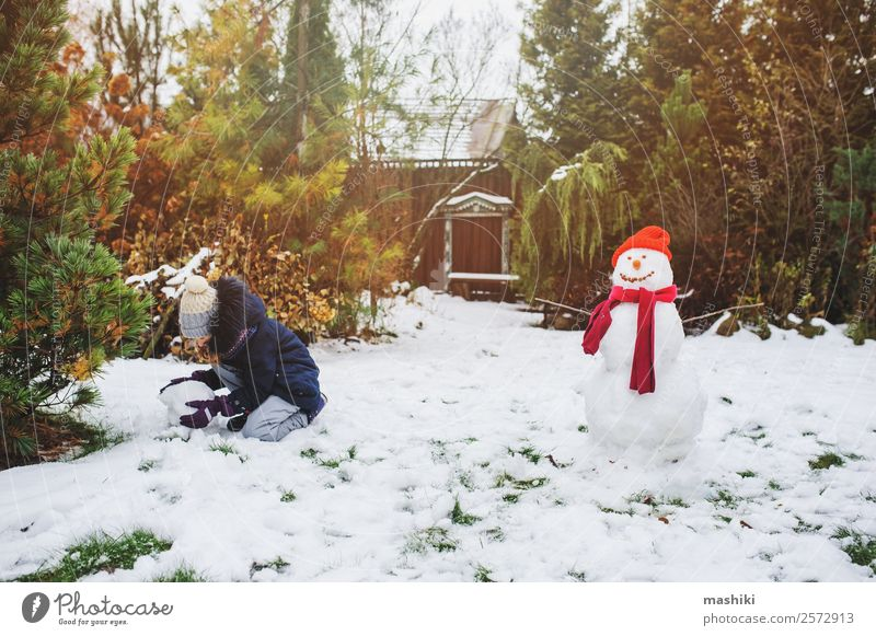 glückliches Kind Mädchen macht Schneemann an Weihnachten Freude Freizeit & Hobby Spielen Ferien & Urlaub & Reisen Winter Garten Natur Wetter Park Bekleidung