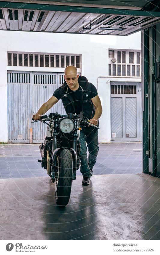 Biker mit dem Motorrad in die Werkstatt Lifestyle Stil Ferien & Urlaub & Reisen Ausflug Mensch Mann Erwachsene Verkehr Straße Fahrzeug Jeanshose Glatze stehen