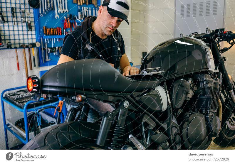 Mechanische Überprüfung des Motorrads Lifestyle Stil Arbeit & Erwerbstätigkeit Mensch Mann Erwachsene Fahrzeug authentisch retro schwarz Mechaniker