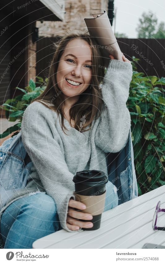 Lifestyle-Porträt einer jungen Frau in grau, die im Freien sitzt. Regen versteckend deckend Handtasche Pullover Jeansstoff Jeanshose PDA Wärme Glück Erholung