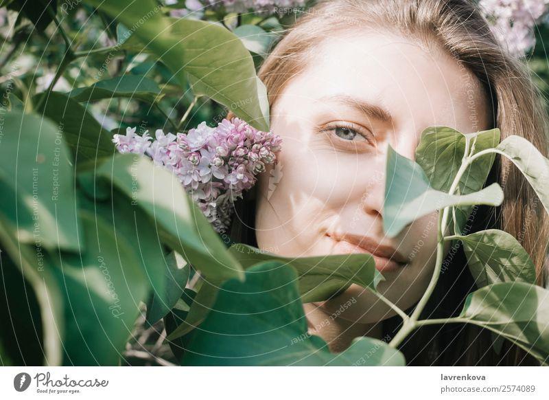 Lifestyle-Porträt einer glücklichen jungen erwachsenen Frau, die Blumen genießt. frisch Park Auge Blatt Fliederbusch Garten Kaukasier hübsch Glück attraktiv