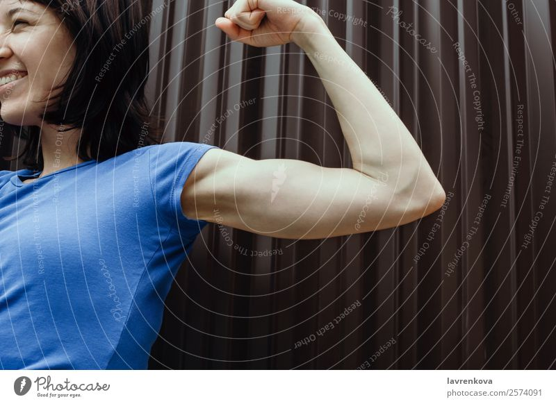 Lächelnde Frau, die ihren Bizeps im Freien beugt, selektiver Fokus. stark dünn Lifestyle Gesundheit Glück Formular Muskulatur Biegung Außenaufnahme Training