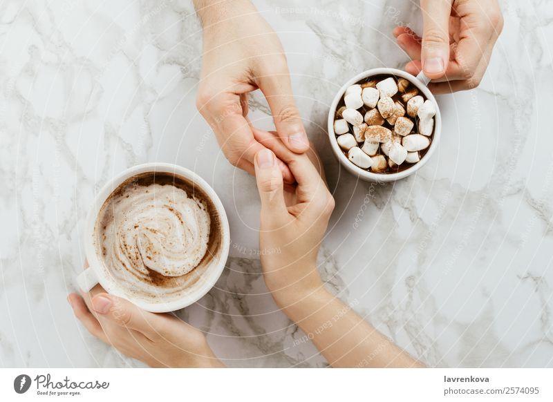 Frau und Mann halten Händchen und zwei Tassen vegane Kakaos. Finger Zusammensein Marmor Morgen Tisch Frühstück Ernährung Hygge Verabredung Herbst Paar Romantik
