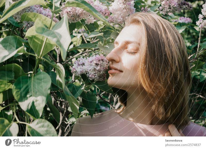 Lifestyle-Porträt einer jungen weißen Frau in fliederfarbenen Blumen aromatisch attraktiv schön Beautyfotografie Sträucher niedlich Gesicht Mode Junge Frau grün