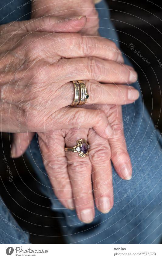 Reife Hände mit Ringen einer Dame liegen auf dem Knie Hand Frau Erwachsene Weiblicher Senior Finger 60 und älter Jeanshose Schmuck alt gepflegt Hautfalten