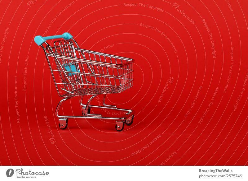 Nahaufnahme eines leeren Spielzeugsupermarktes Einkaufswagen über rot kaufen Wirtschaft Handel Güterverkehr & Logistik Business Metall Kunststoff Farbe