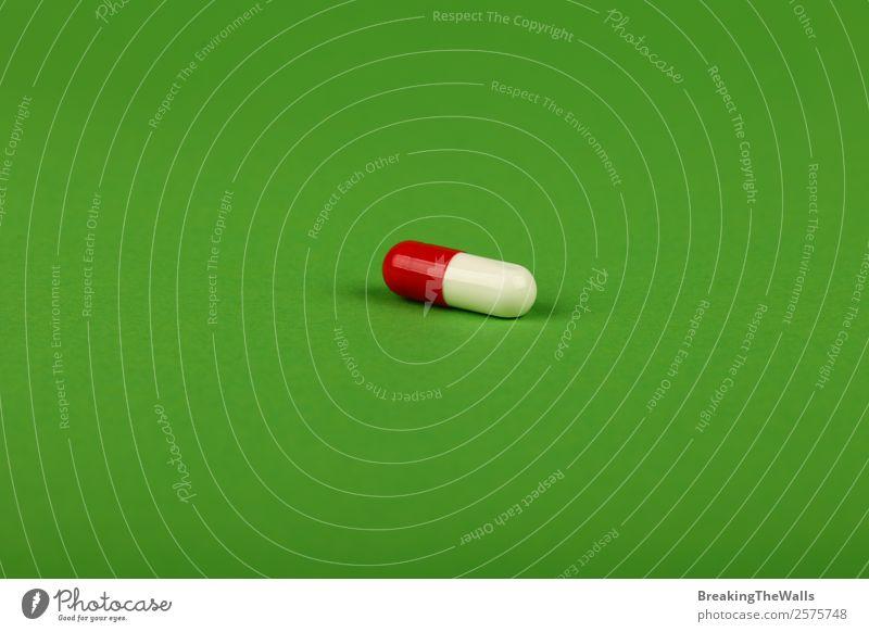 Nahaufnahme einer roten und weißen Gelkappe Pille der Medizin auf Grün Gesundheit Gesundheitswesen Behandlung Rauschmittel Medikament natürlich weich grün Farbe