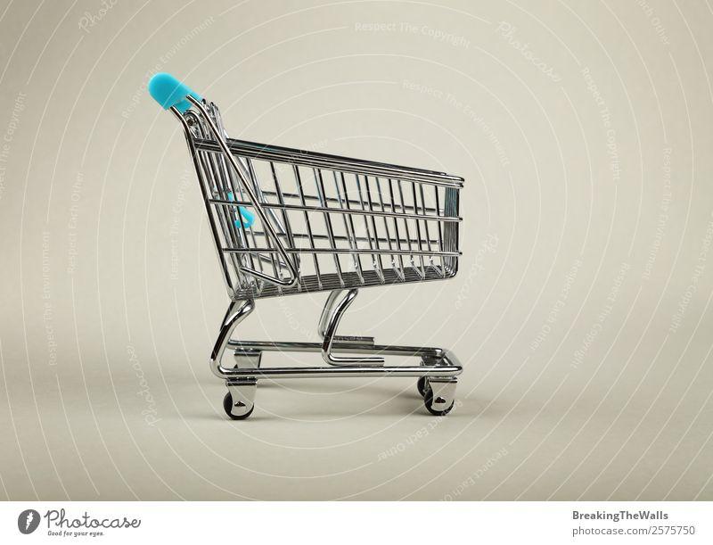 Nahaufnahme des leeren Einkaufswagens im Supermarkt über grauem Hintergrund kaufen Wirtschaft Industrie Handel Güterverkehr & Logistik Business Spielzeug Metall