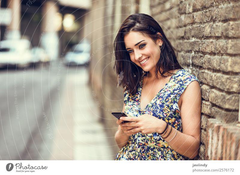 Lächelnde junge Frau, die ihr Smartphone im Freien benutzt. Lifestyle Stil Glück schön Haare & Frisuren Telefon PDA Technik & Technologie Mensch feminin