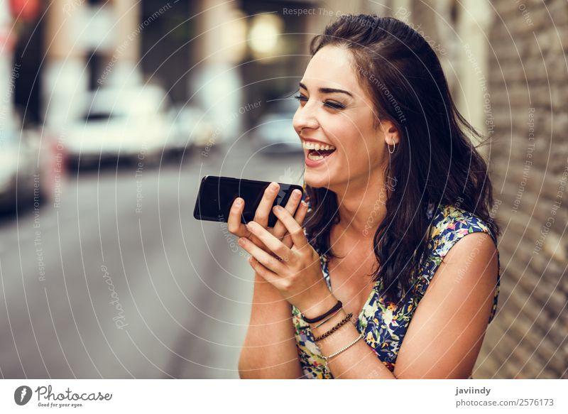 Lächelnde junge Frau, die im Freien mit ihrem Smartphone Sprachnotizen aufzeichnet. Lifestyle Stil Glück schön Haare & Frisuren Telefon PDA