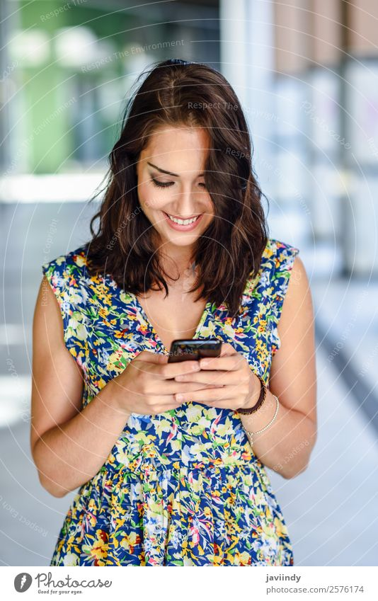 Lächelnde junge Frau beim SMSen mit ihrem Smartphone Lifestyle Stil Glück schön Haare & Frisuren Telefon PDA Technik & Technologie Mensch feminin Junge Frau
