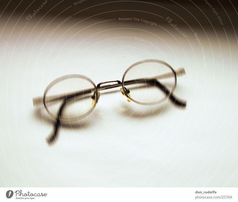 Brille vor Weiß Unschärfe bräunlich Monochrom graphisch Häusliches Leben Glas Schwarzweißfoto
