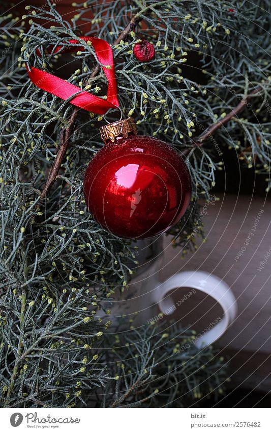 Nostalgische, festliche Weihnachtsdekoration mit zarten Tannenzweigen, roter Kugel und Geschenkband. Rote Weihnachtskugel hängt glänzend an Zweigen. Leuchtende Christbaumkugel aufgehängt an Ästen in alter weisser, nostalgischer Kanne aus Porzellan zuhause.