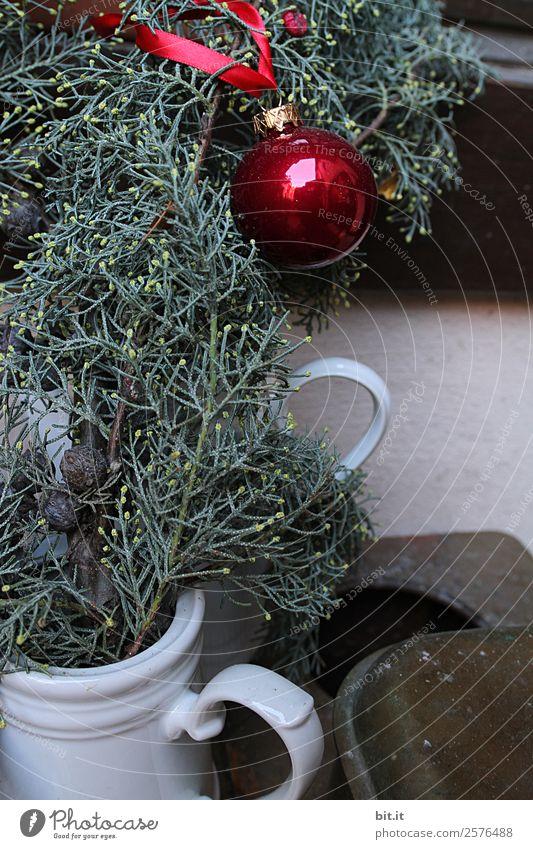 Nostalgische Weihnachtsdekoration mit zarten Tannenzweigen, roter Kugel und Vasen auf altem Tisch. Rote Weihnachtskugel hängt glänzend an Zweigen. Leuchtende Christbaumkugel aufgehängt an Ästen in alten weissen, nostalgischen Kannen aus Porzellan zuhause.