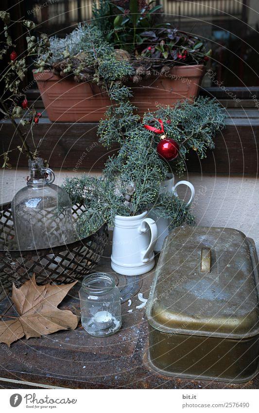 Rustikale, schöne Weihnachtsdekoration mit Zweigen und Christbaumkugel, auf altem, vintage Tisch im Winter zur Adventszeit. Gesteck zu Weihachten mit Blumentopf, Teelicht, Glasvase, Pflanzen, Hangebutte auf altem Herd, draussen im kalten, eisigenGarten.