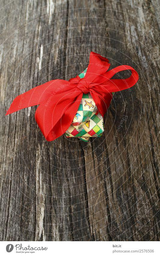Weihnachtsgeschenk mit roter Schleife auf Holz alt Weihnachten & Advent Freude Glück Feste & Feiern braun Freundschaft Häusliches Leben Dekoration & Verzierung
