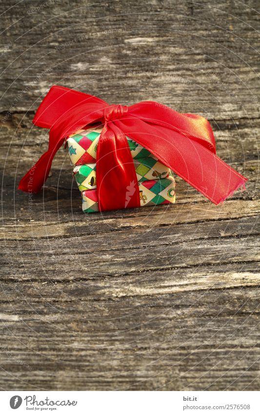 bunte Weihnachtspäckchen verpackt mit Weihnachtspapier mit roter Schleife, auf rustikalem Holz. Weihnachtsgeschenke, liegen hübsch dekoriert mit Band auf Holztisch. Viele Weihnachtspäckchen mit Geschenkpapier mit Weihnachtsmotiv. Konzept Geschenke Advent.
