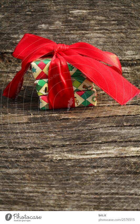 Überraschung l bunte Weihnachtspäckchen verpackt mit Weihnachtspapier mit roter Schleife, liegen auf rustikalem Holz. Weihnachtsgeschenke, liegen hübsch dekoriert mit Band auf Holztisch. Viele Weihnachtspäckchen mit Geschenkpapier mit Weihnachtsmotiv.