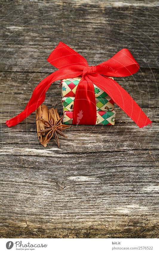 Überraschung l bunte Weihnachtspäckchen verpackt mit Weihnachtspapier mit roter Schleife, Zimt, Sternanis liegen auf rustikalem Holz. Weihnachtsgeschenk, liegt hübsch dekoriert mit großer Schleife aus rotem Band und weihnachtlichen Gewürzen auf Holztisch.