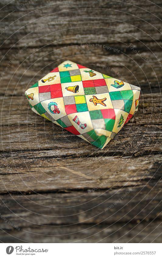 Überraschung l kleines, buntes Weihnachtspäckchen verpackt mit Weihnachtspapier liegt auf rustikalem Holz.Weihnachtsgeschenk, verpackt in Papier mit weihnachtlichen Motiven . Niedliches Weihnachtspäckchen mit Geschenkpapier mit Weihnachtsmotiven eingepackt