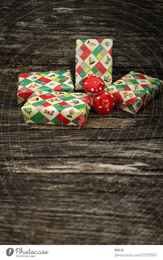 Überraschung l viele, bunte, umhüllte Weihnachtspäckchen & Pilze, liegen auf altem rustikalen Holztisch als Dekoration und Verzierung. Kleine Weihnachtsgeschenke in Geschenkpapier mit Weihnachtsmotiv verpackt, warten unterm Weihnachtsbaum aufs Auspacken.