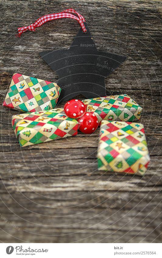 viele, bunte, umhüllte Weihnachtspäckchen, Tafel, Stern & Pilze, liegen auf altem rustikalen Holztisch als Dekoration und Verzierung. Kleine Weihnachtsgeschenke in Geschenkpapier, vor Schiefertafel, Blanko, Schild sternförmig, schwarz,leer zum Beschriften.