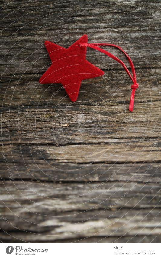 Frohe Weihnachten. Roter Stern aus Filz mit Band, liegt auf altem Holz. Roter Weihnachtsstern, als Dekoration auf rustikalem, braunen Holzbrett. Filz-Stoff-Stern als Schild, Blanko, Anhänger, Aufhänger auf braunem, rustikalem  Holztisch, Textfreiraum.