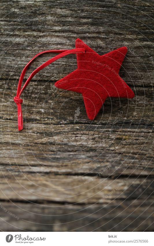 Frohe Weihnachten, ihr Lieben! Roter Stern aus Filz mit Band, liegt auf altem Holz im Vintage-Stil. Roter Weihnachtsstern, als Dekoration auf rustikalem, braunen Holzbrett. Filz-Stoff-Stern als Schild, Weihnachtsbaum-Anhänger, Blanko, Deko zur Adventszeit.