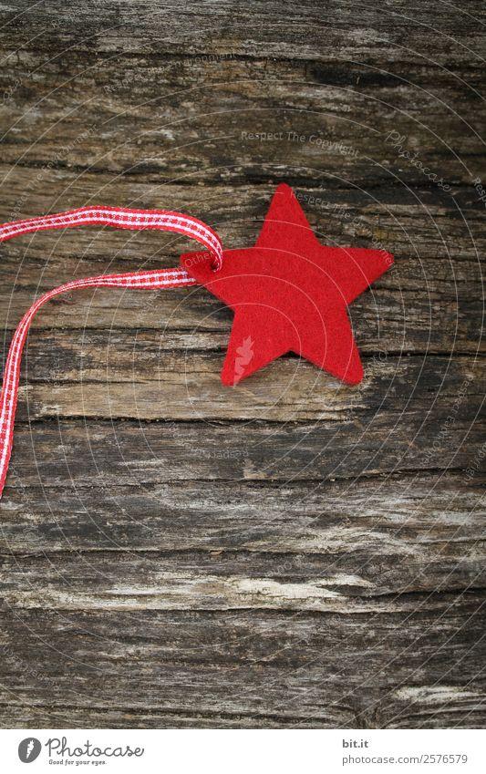 Frohe Weihnachten. Roter Stern aus Filz mit Band, liegt auf altem Holz. Roter Karo-Weihnachtsstern, als Dekoration auf rustikalem, braunen Holzbrett. Filz-Stoff-Stern als Schild, Blanko, Anhänger, Aufhänger auf braunem, rustikalem Holztisch, Textfreiraum.