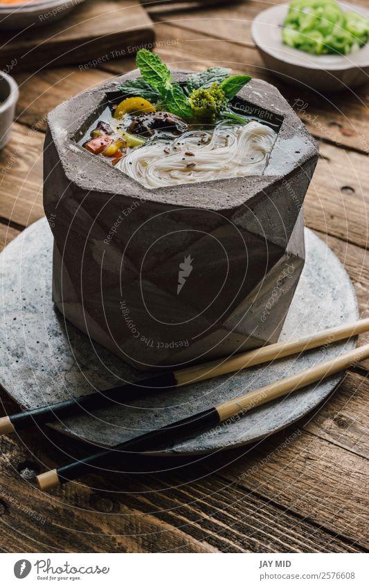 Geometrische Schale aus asiatischer Nudelsuppe mit Essstäbchen Lebensmittel Fleisch Gemüse Teigwaren Backwaren Suppe Eintopf Mittagessen Abendessen