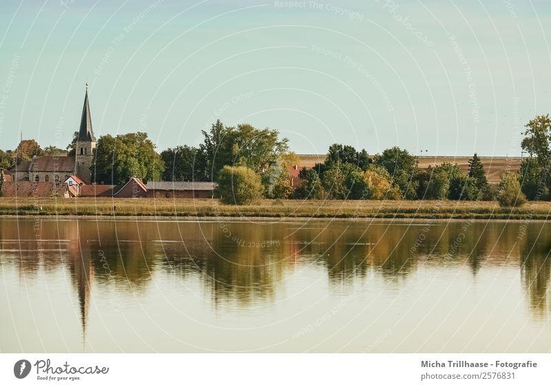 Dorf am See Natur Landschaft Wasser Himmel Wolkenloser Himmel Sonnenlicht Herbst Schönes Wetter Baum Sträucher Kirchturm Haus Kirche Erholung glänzend leuchten